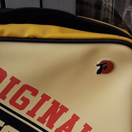 a cream yellow and red bag that says ORIGINAL and has an F Plus pin