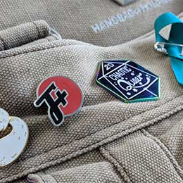 An F Plus pin sharing space on a backpack with a pin that says It Will Be Okay and a pin that says Chaotic Queer, also a teal ribbon