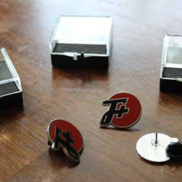Three F Plus pins in different positions next to their cases