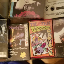 Audio Garbage cassette next to Prince's Purple Rain and other tapes from the 80's