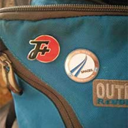 An F Plus pin on a Outdoor backpack next to a Official Team Space IL pin
