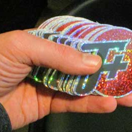 a stack of glittery f plus logo stickers in a human hand