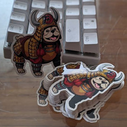 a stack of samurai dog stickers against a white keyboard